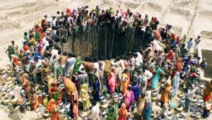 "People gather to get water from a huge well in the village of Natwarghad in the western Indian state of Gujarat on June 1, 2003. Natwargadh is in the midst of the worst drought in over a decade. Dams, wells and ponds have gone dry across the western and northern parts of Gujarat forcing people to wait for hours around village ponds for the irregular state-run water tankers to show up as the temperature sores to over 44 degree Celcius. The United Nation's World Environment Day will be celebrated on Thursday with the theme of ""Water - Two Billion People are Dying for It"". REUTERS/Amit Dave BEST QUALITY AVAILABLE - RTR1FD9Y"